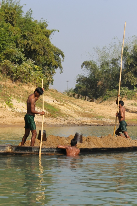 Bangladeshi men fish for sand from India.
