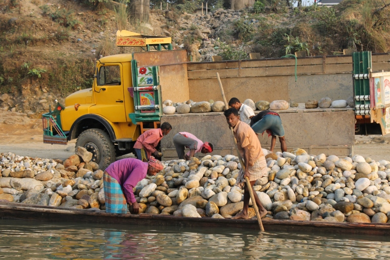 Moving rocks from river to boat to truck.