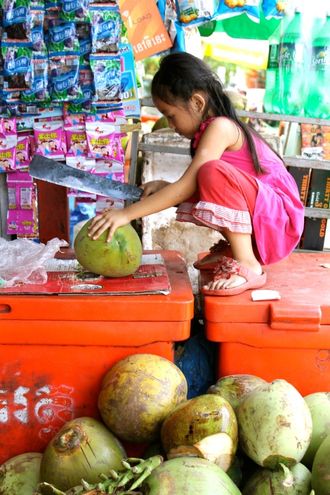 This little girl hacked away happily at this coconut with her machete.