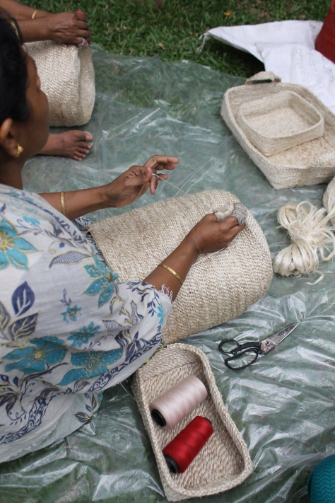 Lady sewing jute bags.