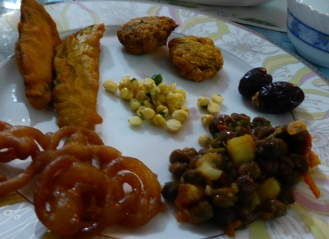 My iftar plate. From the top: pakora, dates, lentil salad, jalallopy, deep fried eggplant, and in the center, split pea salad.