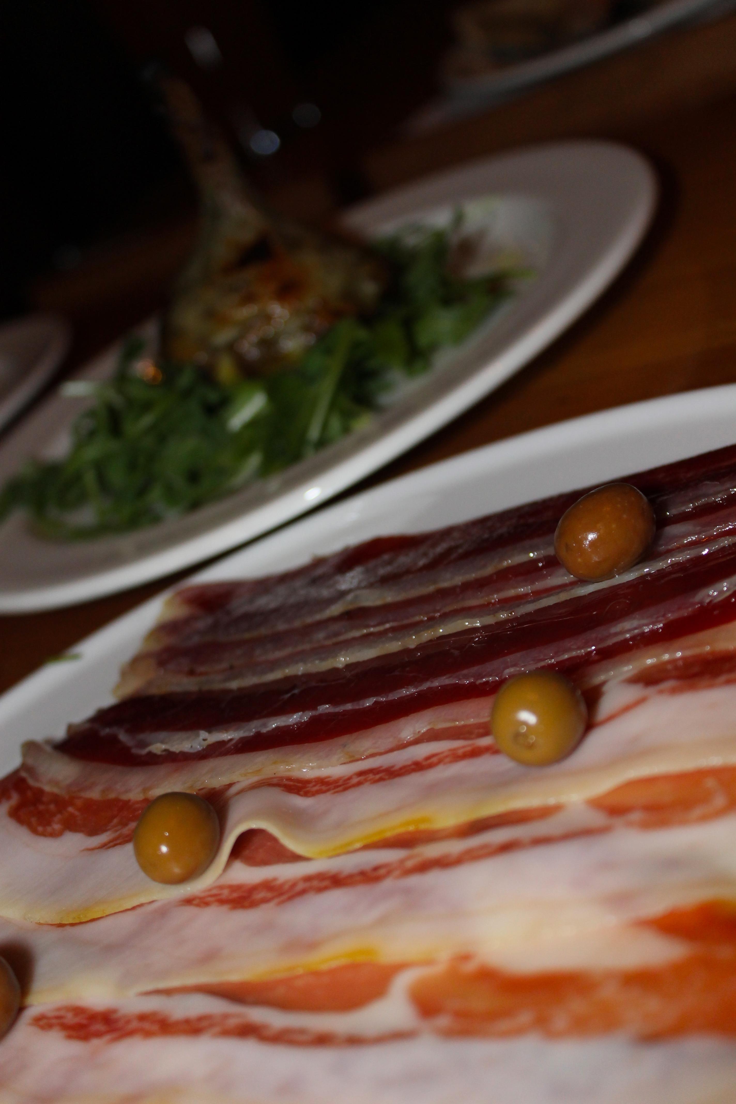 Three kinds of fancy ham and a stuffed artichoke.