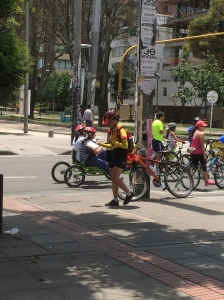 A worker at an intersection and various types bikes behind her. The green one is a four person bike.